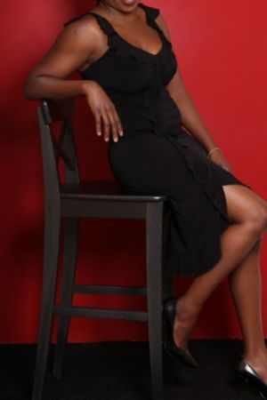 Lindy on chair with long black dress.