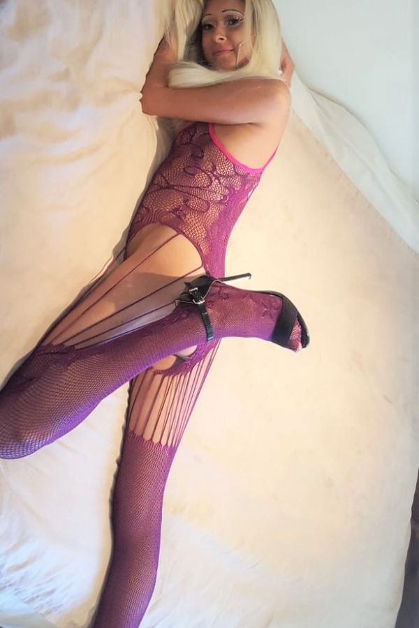 Stacey lying in bed wearing hot purple lingerie set.