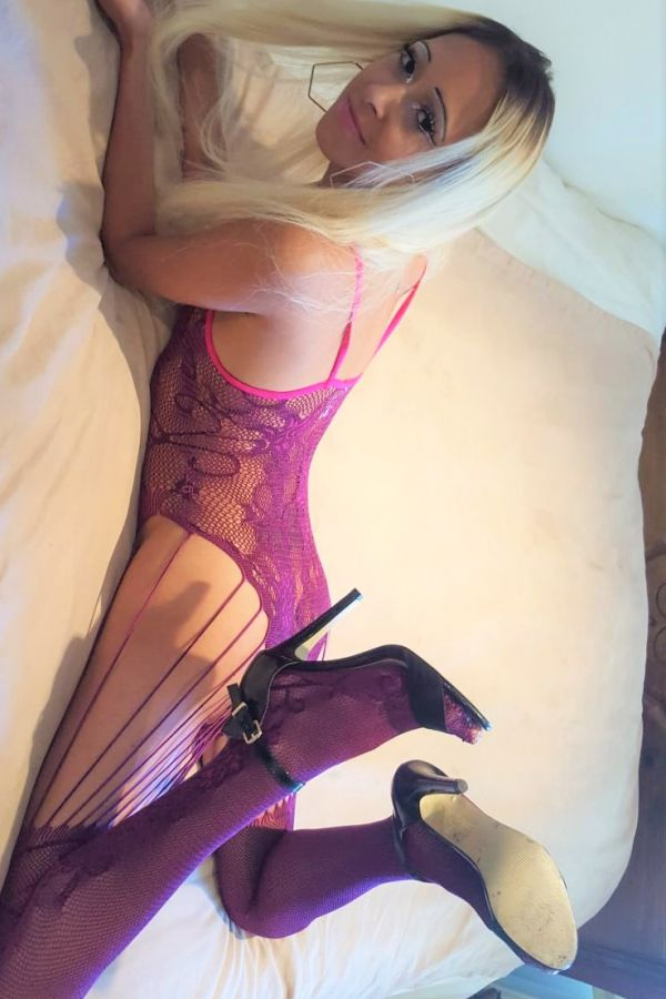 stacey lying on bed in sexy purple lingerie set and stockings.